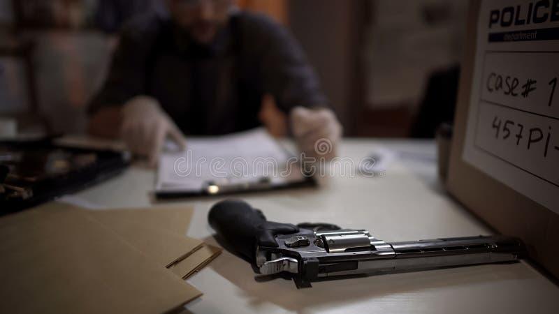 Detective del hombre que examina el arma del revólver y que llena la investigación del informe de la experiencia fotos de archivo libres de regalías