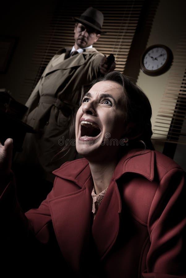 Detective die een kanon richten aan een angst aangejaagde vrouw stock afbeeldingen