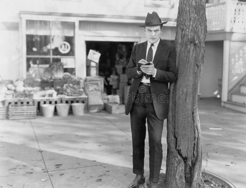 Detective die tegen boom leunen die nota's nemen stock afbeelding