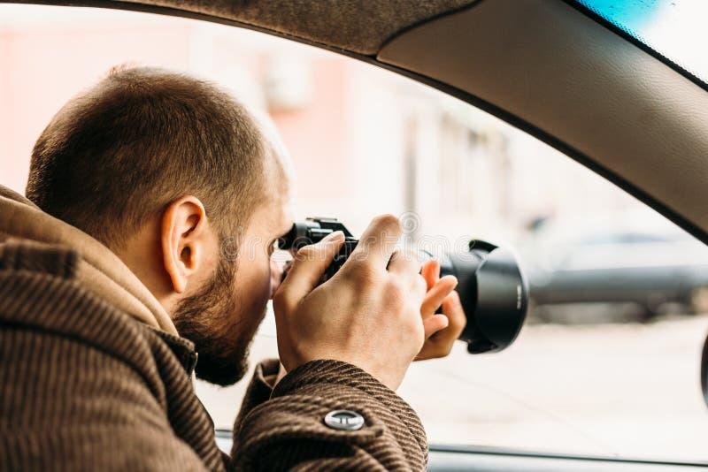 Detective privado o reportero o paparazzis que se sienta en coche y que toma la foto con la cámara profesional imágenes de archivo libres de regalías