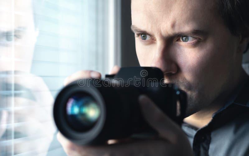 Detective privado, poli secreto, investigador, espía o paparazzis con la cámara que toma las fotos Espionaje del agente o de la p foto de archivo