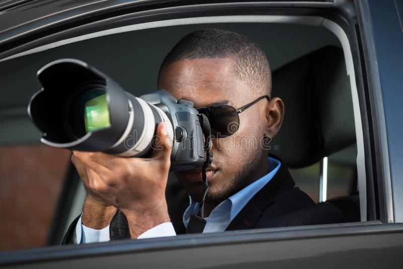 Detective Sitting Inside Car Photographing. Private Detective Sitting Inside Car Photographing With SLR Camera stock photos