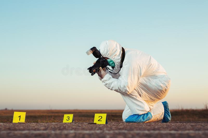 Detective studying a crime scene taking photographs. Young Detective studying a crime scene taking photographs stock image