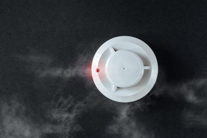 Detector de fumo e detector de fogo em um fundo preto Configuração lisa do alarme de incêndio imagem de stock royalty free
