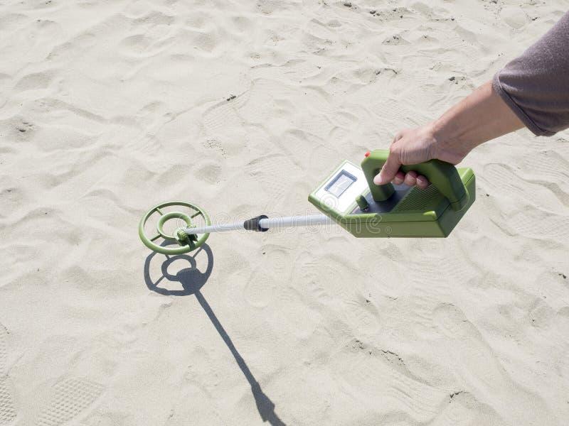 Detector de metales que busca para los tesoros en una playa arenosa imagen de archivo libre de regalías
