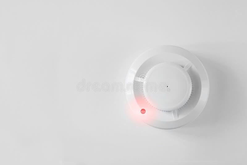 Detector del detector de humo y de incendios en un fondo blanco Endecha plana la alarma de incendio foto de archivo libre de regalías