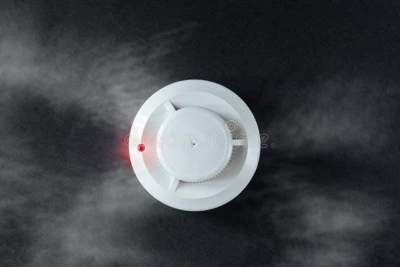 Detector del detector de humo y de incendios en un fondo negro Endecha plana la alarma de incendio imagen de archivo