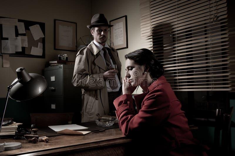 Detektiv, der eine junge nachdenkliche Frau in seinem Büro interviewt stockfotografie