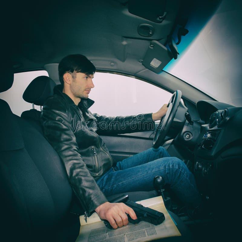 Detektiv mit einem Gewehr, das in einem Auto sitzt stockfoto