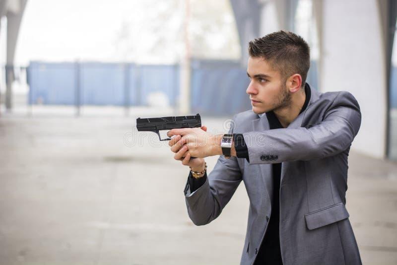 Detektiv oder Gangster oder Polizist, die eine Feuerwaffe zielen stockfoto