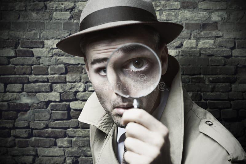 Detektiv- se för tappning till och med en förstoringsapparat royaltyfri foto