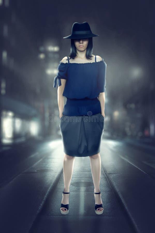 Detektywistyczna kobieta zatrzymuje w ulicie przy nocą i spojrzeniami w kamerze w zdjęcia royalty free