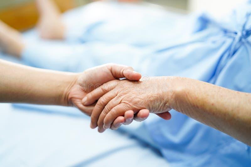 Detener al paciente mayor de las manos conmovedoras o mayor asi?tico de la mujer de la se?ora mayor con amor, cuidado, ayudando,  imagenes de archivo