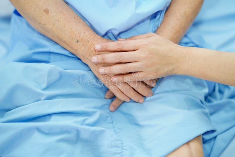Detener al paciente mayor de las manos conmovedoras o mayor asi?tico de la mujer de la se?ora mayor con amor, cuidado, ayudando,  imagen de archivo libre de regalías