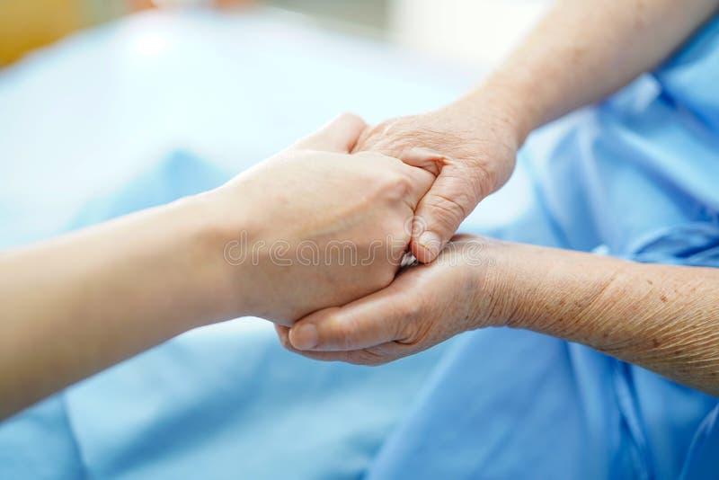Deteniendo al paciente mayor de las manos conmovedoras o mayor asi?tico de la mujer de la se?ora mayor con amor, el cuidado, ayud fotografía de archivo libre de regalías