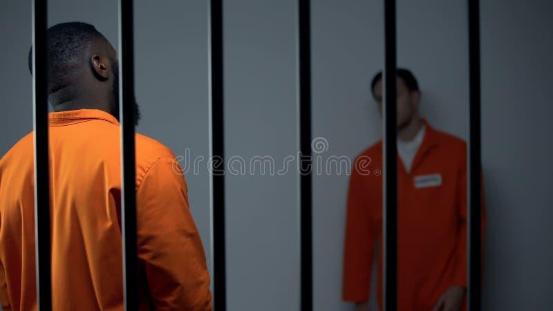 Detenuti in cella di prigione che si guardano l'un l'altro, malintesi e conflitti immagini stock