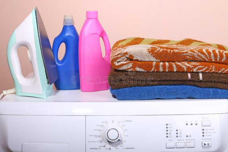 Detergens, handdoeken en een wasmachine met een belangrijk punt in het leven van een duidelijke achtergrond stock afbeelding
