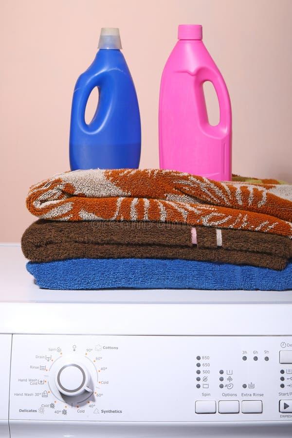 Detergent, ręczniki i pralka z punktem kluczowym w życiu prosty tło, zdjęcie stock