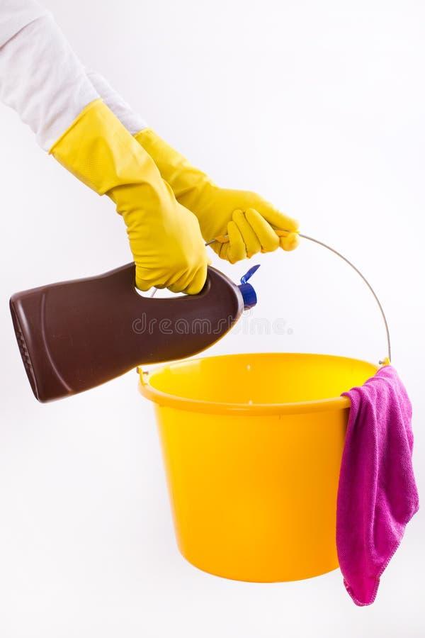 Detergente de derramamento da mulher na cubeta no fundo branco fotografia de stock