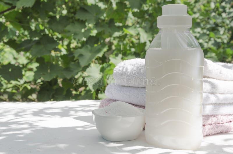 Detergente para a roupa, toalhas lavadas frescas na superfície branca à sombra das folhas fotos de stock