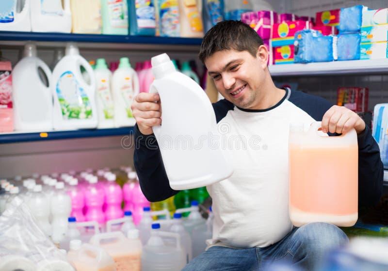 Detergentes de compra do cliente para a lavanderia imagens de stock royalty free