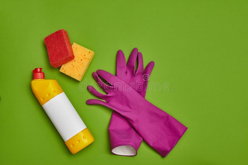 Detergents and cleaning accessories on a green background. Housekeeping concept. royalty free stock photo