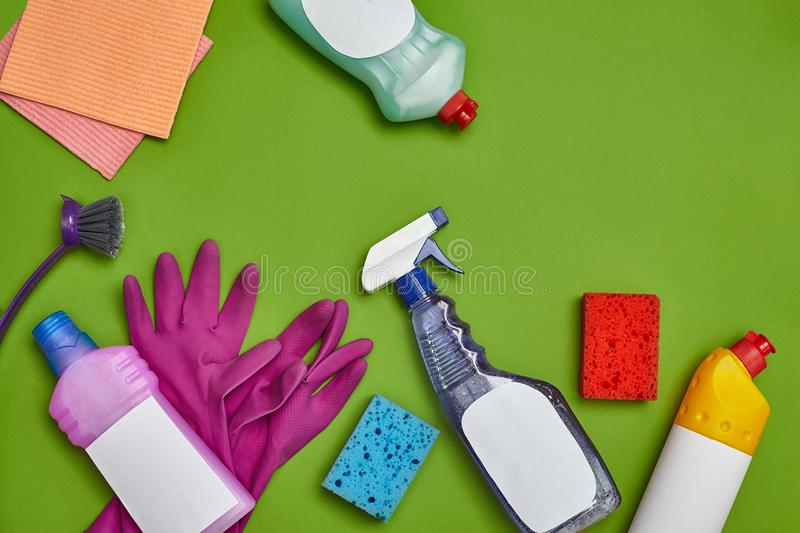 Detergents and cleaning accessories on a green background. Housekeeping concept. stock images
