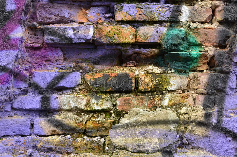 Deteriorated painted brick wall. Old deteriorated brick wall airbrushed with purple paint royalty free stock images