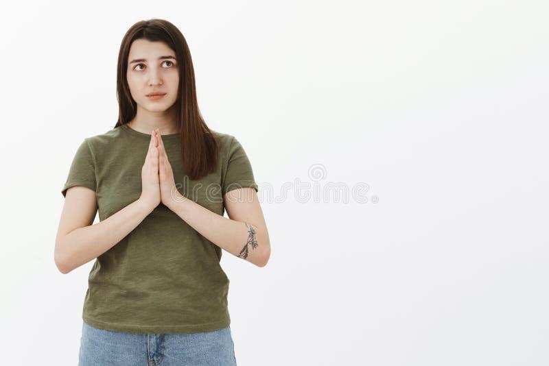 Determinado e sério-olhando a menina 20s nova com a tatuagem que guarda as mãos rezar dentro sobre o corpo que olha o canto direi imagem de stock