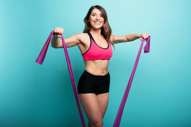 Determinated girl trains with elastic for gym. Happy and joyful expression. Cyan background. Determinated attractive girl trains with elastic for gym. Happy and stock photos