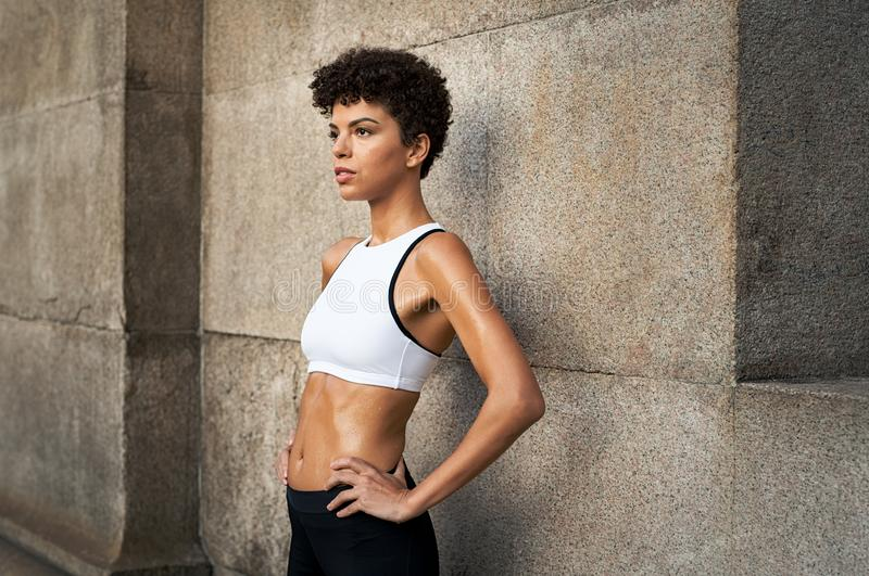 Determinated sporty woman resting on wall stock photo