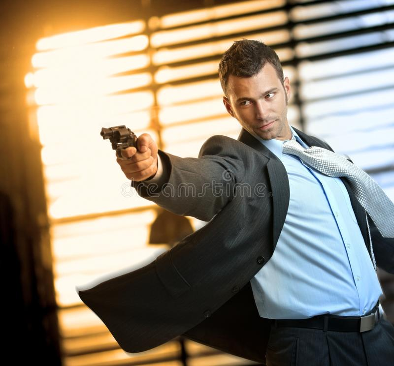 Determined action hero wearing suit holding gun. Determined caucasian action hero wearing suit and tie holding gun in hand. Standing, moving, aiming with royalty free stock image