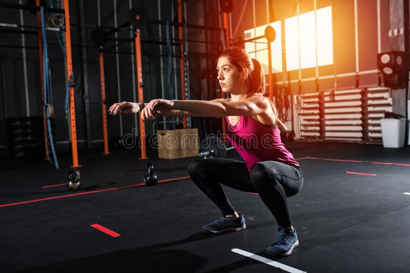 Athletic girl does squat exercises at the gym stock image