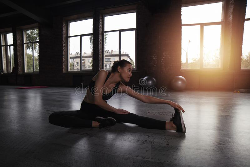 Athletic girl does stretching exercises at the gym royalty free stock image