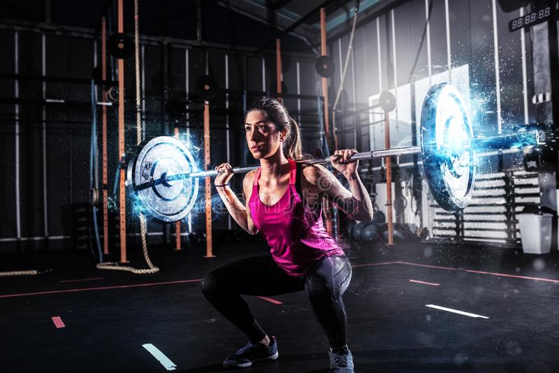 Athletic girl works out at the gym with a barbell with blue energy effects stock photography
