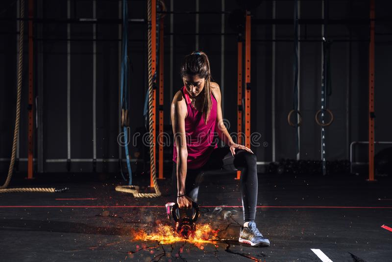 Athletic girl works out at the gym with a fiery kettlebell royalty free stock images