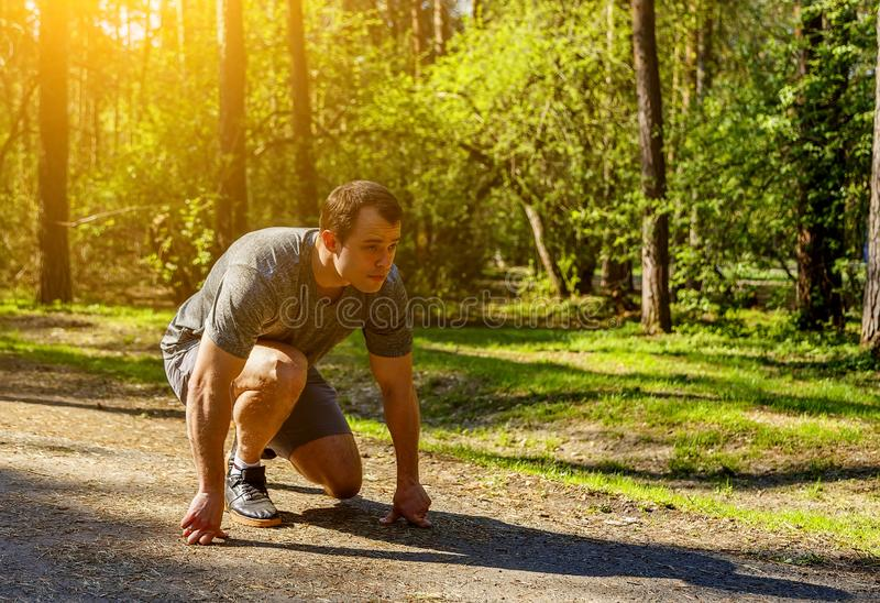Determined Caucasian sprinter preparing to start racing on road in park. Man runner on start position. Sportsman on concentrated royalty free stock photo