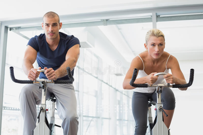 Determined fit couple working on exercise bikes at gym. Determined fit young couple working on exercise bikes at the gym stock images