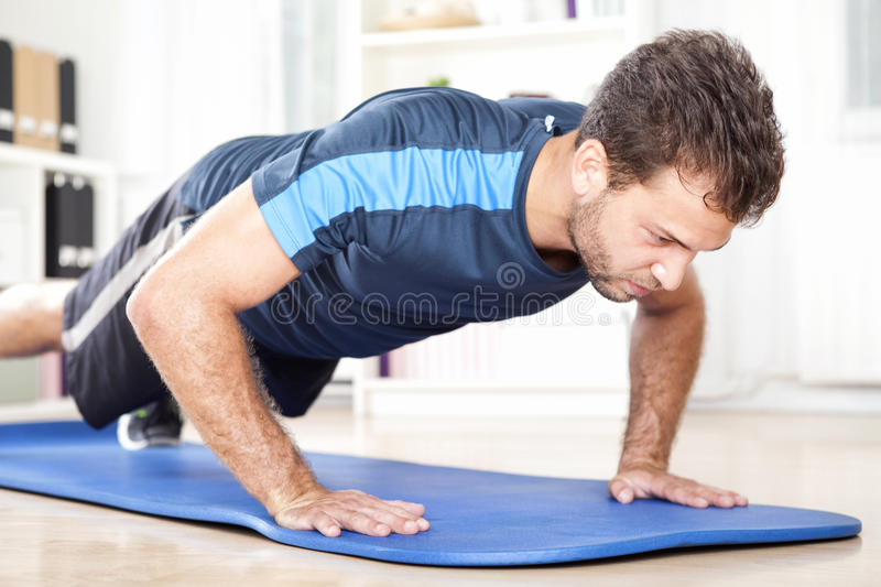 Determined Fit Young Man Doing Planking Exercise stock photos