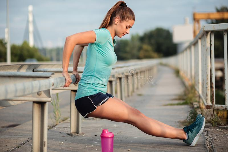 Determined fit young woman exercising on a bridge royalty free stock photography