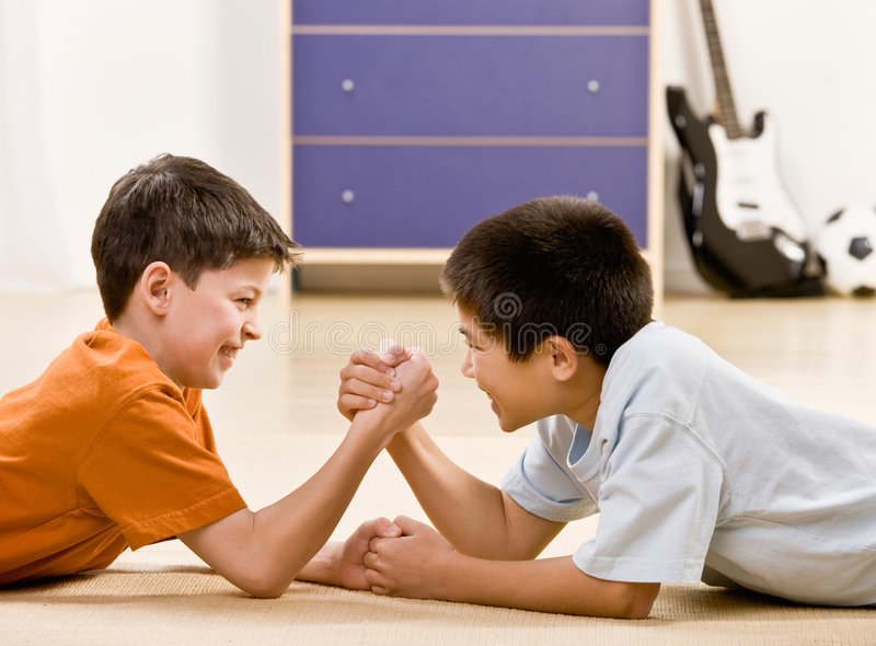 Determined friends arm wrestle. Smiling stock image