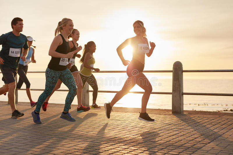 Determined group of young people running in city stock image