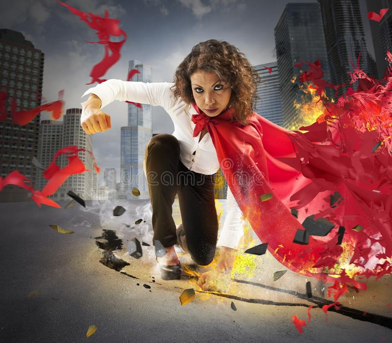 Determined hero businesswoman. Hero businesswoman gives a fist on asphalt stock photography