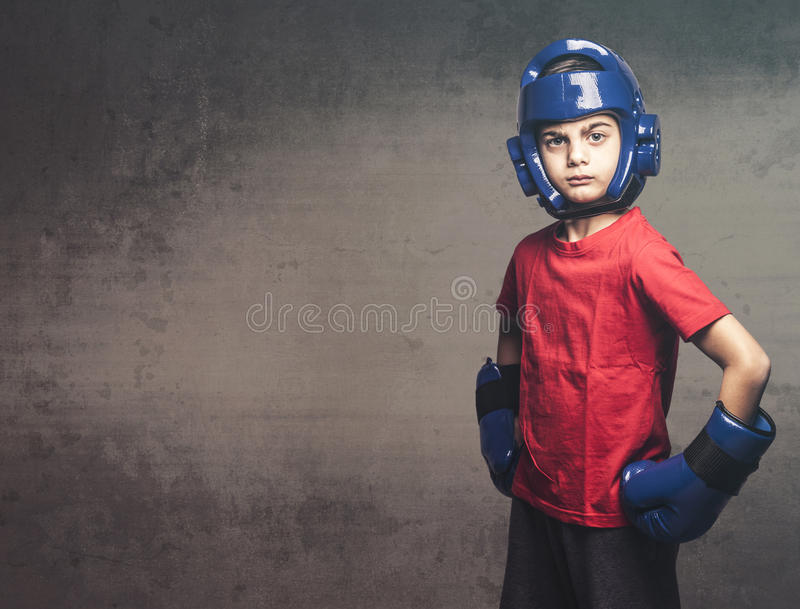 Determined little fighter. Young boy wearing blue gloves and helmet. Martial arts kids concept stock image