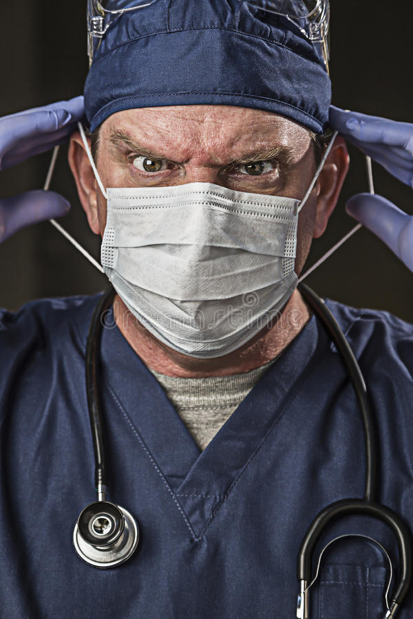 Determined Looking Doctor or Nurse with Protective Wear and Stet. Determined Looking Male Doctor or Nurse with Protective Wear and Stethoscope royalty free stock photo