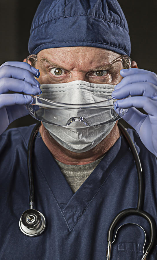 Determined Looking Doctor or Nurse with Protective Wear and Stet. Determined Looking Male Doctor or Nurse with Protective Wear and Stethoscope stock photo