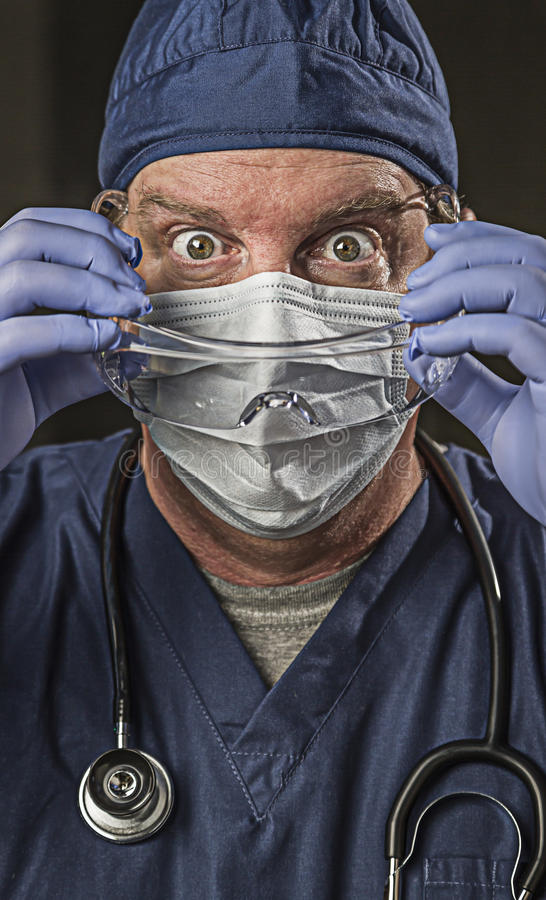 Determined Looking Doctor or Nurse with Protective Wear and Stet. Determined Looking Male Doctor or Nurse with Protective Wear and Stethoscope stock image