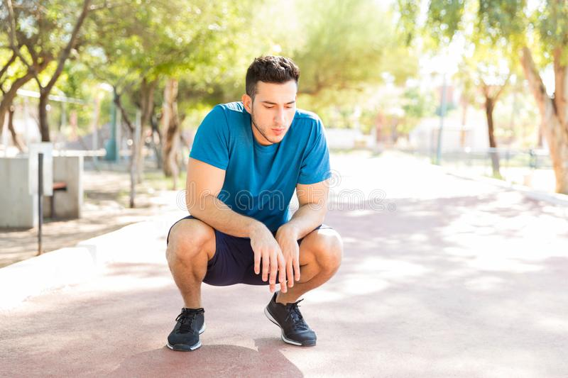 Determined Runner Crouching On Track After Workout In Park. Determined male runner crouching on track after workout in park royalty free stock images