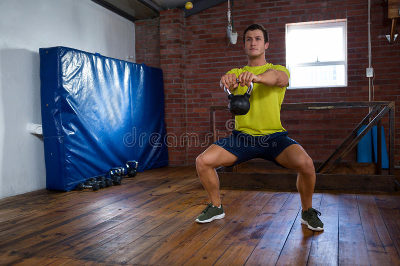 Determined man exercising with kettlebell stock photography