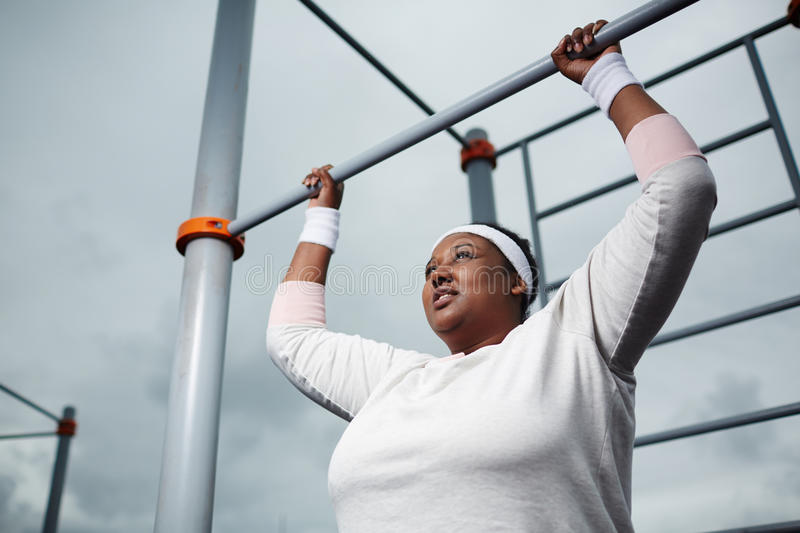 Determined overweight African woman practicing pull-up exercise outdoors stock image